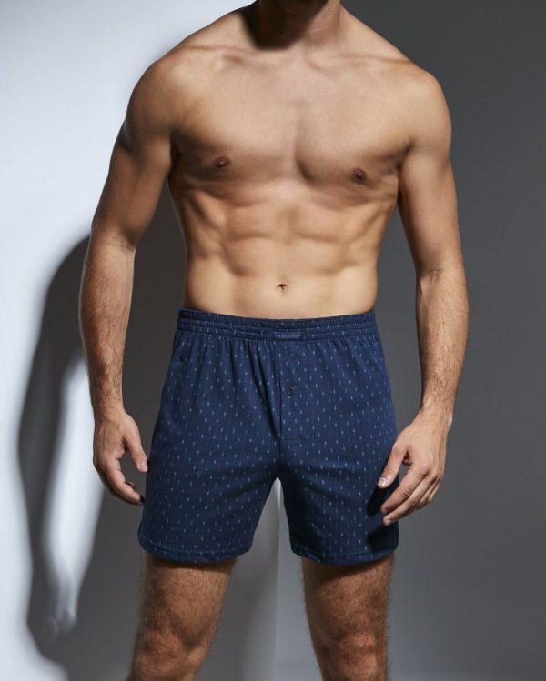 Boxer shorts para homem, com estampado formas geométricas azuis e vermelhas sobre um fundo azul marinho., são suaves ao toque e apresentam um design casual e confortável.